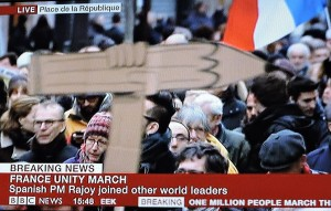Marchers in Paris hold a giant pencil