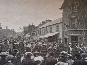 The 1907 procession showing, on the cottages, some of the decorative shields